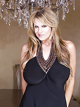 Toys Pics: Kelly wears a black dress and plays with her pussy on the dinning room table.